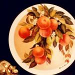 piatto porcellana con arance su fondo metallizzato